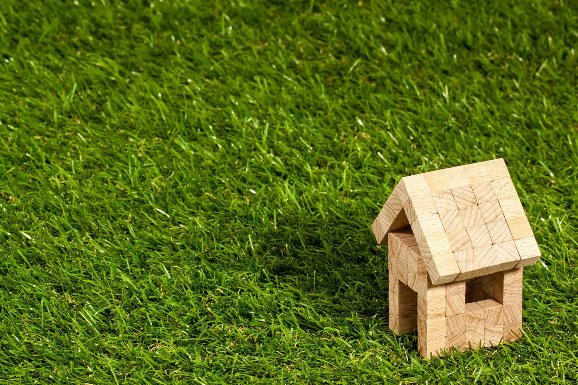 Small toy house made of little wooden cubes sitting on a lawn
