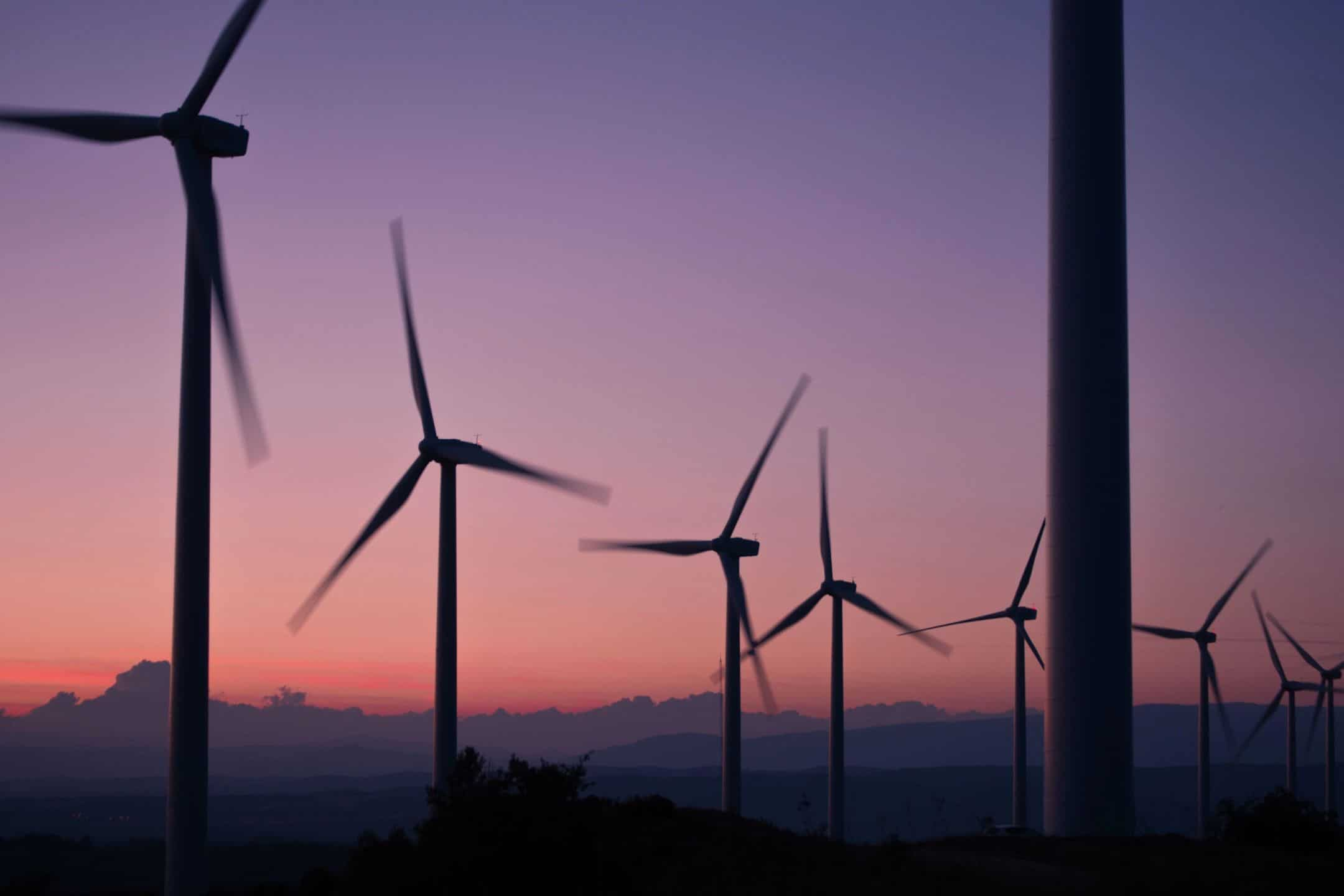 Wind turbines at dusk, a purple red colour in the sky