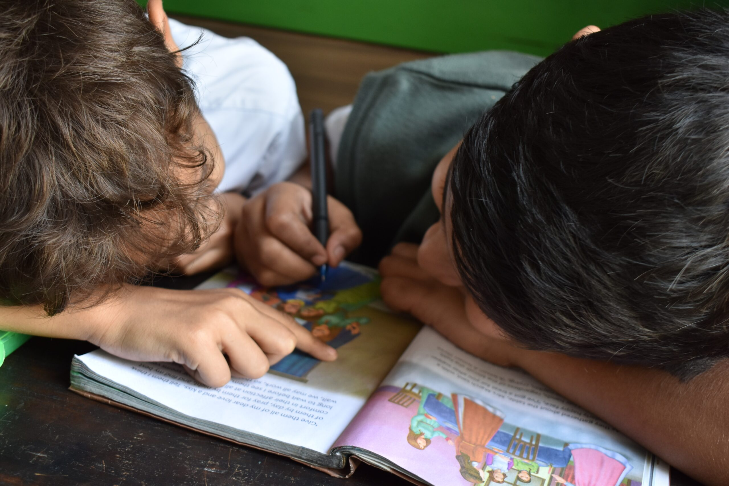 2 children writing in a book, learning together
