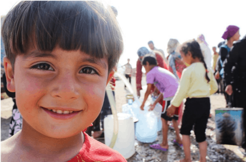 Little boy looking at the camera in a refugee camp. In the background children fill water bottles