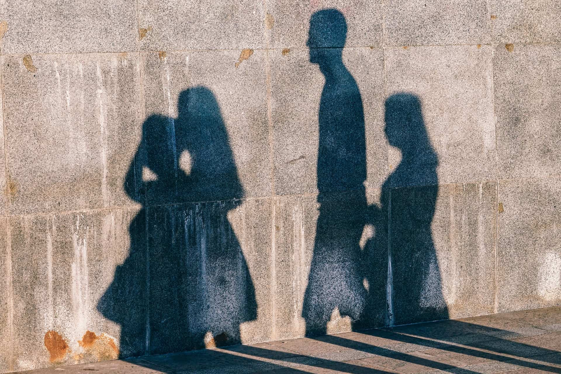 Silhouette of a family on a brown/grey wall