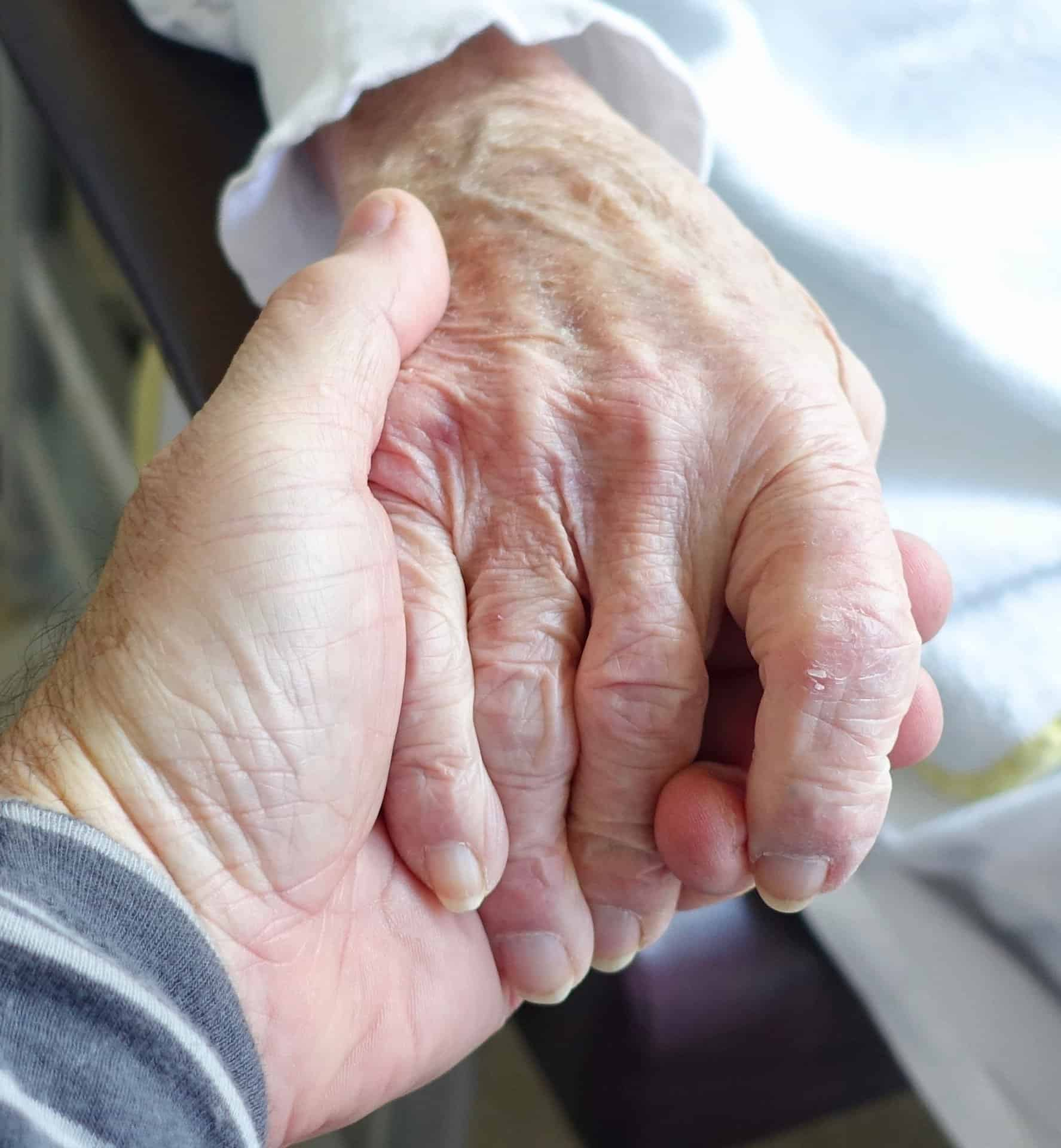 Man holding gently an old woman's hand