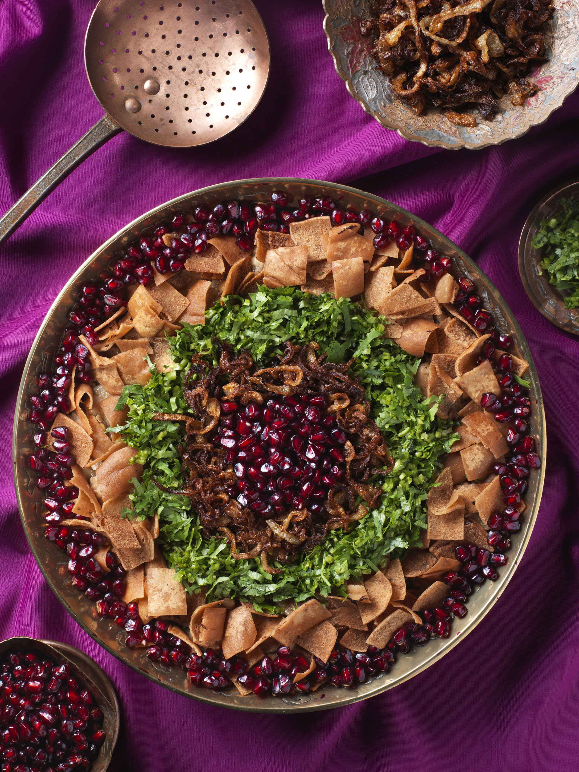 Dish with pomegratete seeds, onions and aubergine laid down on a purple cloth.
