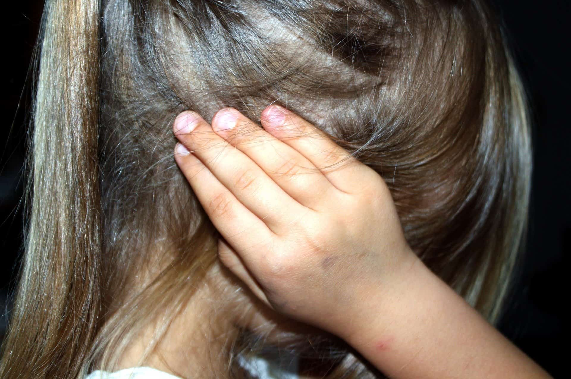 Little girl with brown hair covering her ears