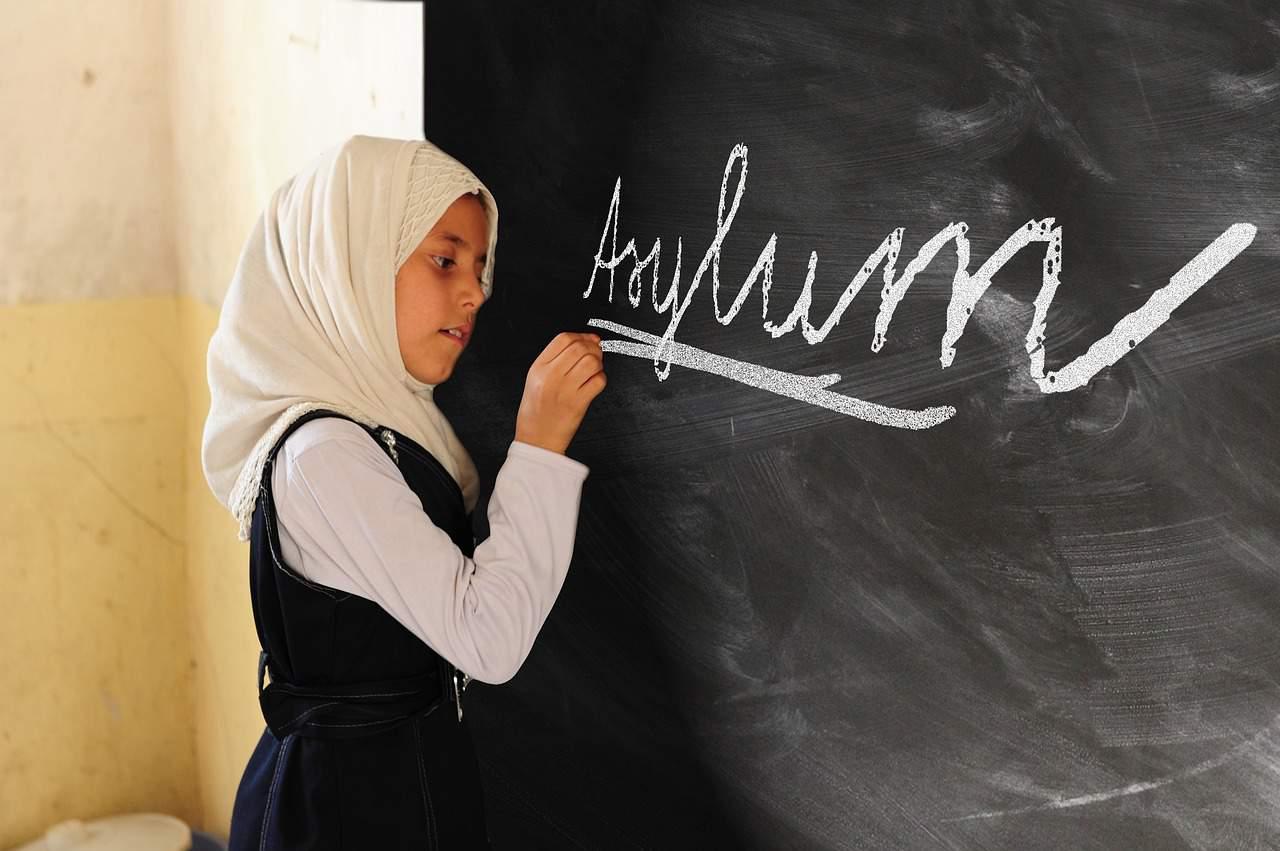 The word asylum written on a blackboard in chalk by a young girl wearing a head scarf