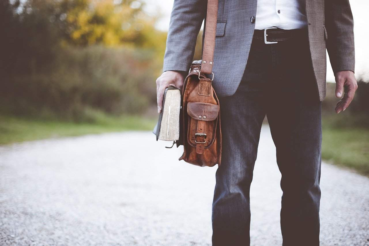 Smartly dressed man walking holding a book