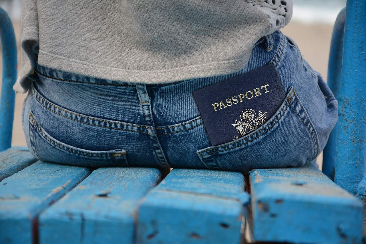 Blue passport poking out of the back pocket of a woman's jeans