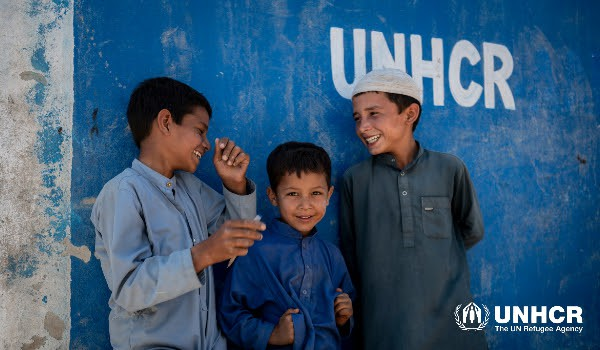 Three boys laughing together in front of a UNHCR stencilled blue wall
