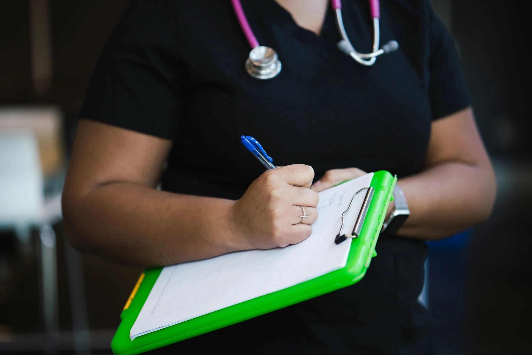 Photograph of a nurse holding a clipboard and writing notes
