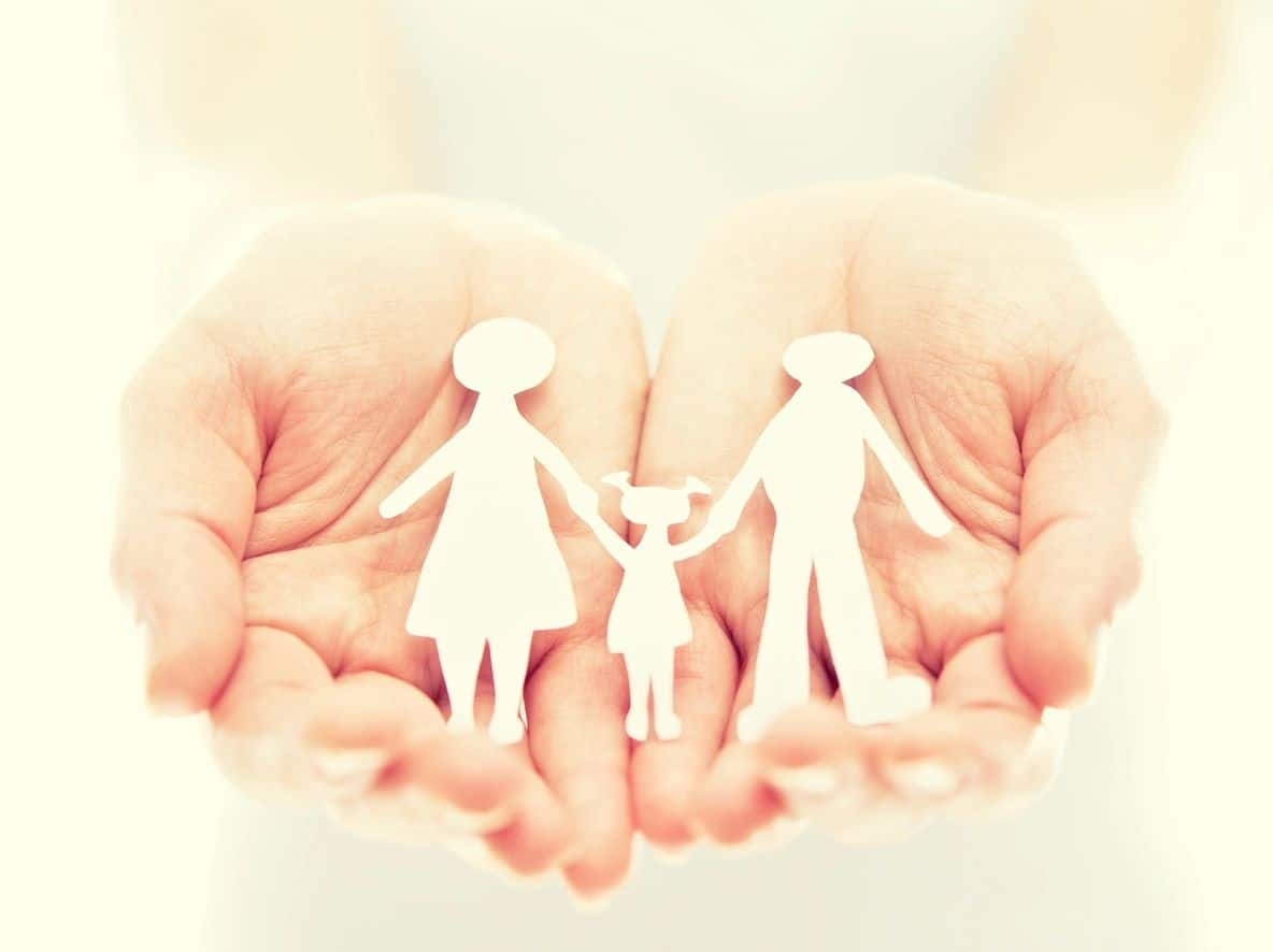 Open hands with a paper cut-out of a family
