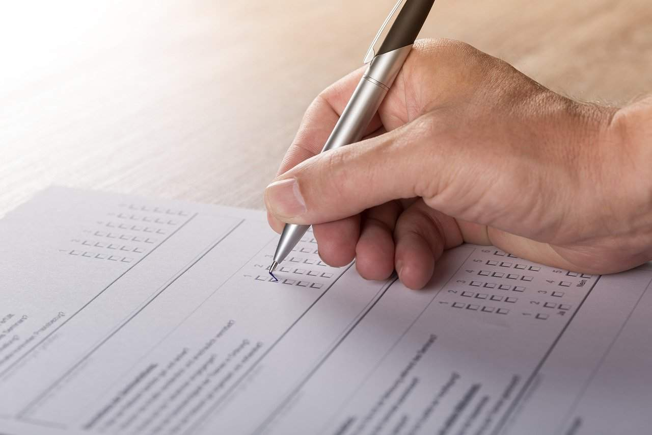 A hand filling out a printed survey form